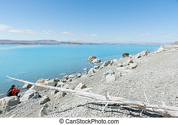A tourist at Lake Pukaki, NZ - The turquoise water, blue sky...