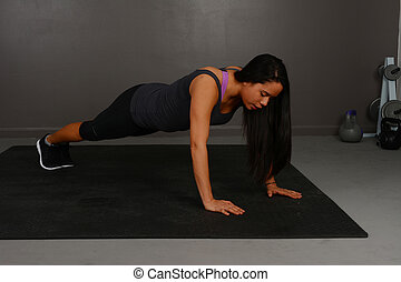 Gym exercise - Female doing pushup workout in indoor gym
