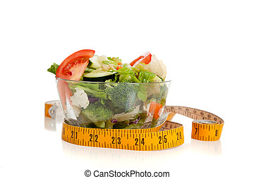 Tossed salad and tape measure on white - A tossed salad...