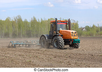 Tillage - Tractor with a cultivator plowing the field in the...