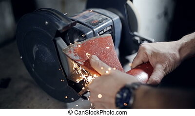 Close up the hands of a blacksmith sharpening axe on electrical grinder beautiful sparks