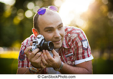 man and the old camera - cheerful young couple relaxing in...