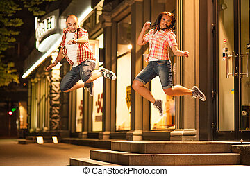 jump, couple - cheerful young couple relaxing in the park on...