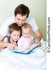 Family reading - Young father and two kids reading book in...