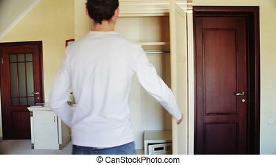 Man opens an empty wardrobe in which only empty hangers. -...