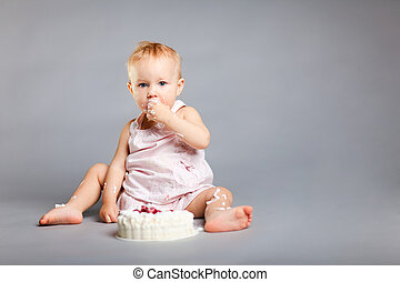 Birthday cake - Cute little girl eating her first birthday...