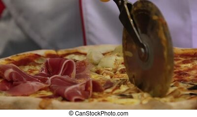 Hands chef cuts italian pizza with mushrooms, ham, pineapple and cheese