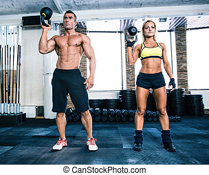 Muscular man and fit woman workout with kettle ball at gym