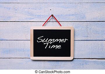 Summer time - Blackboard hanging with Summer time phrase on...