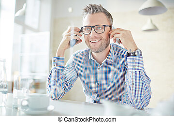 Man with smartphones - Smiling businessman in eyeglasses...