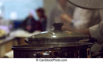 Close up of hands chef opens the pot filling pan with water...