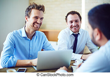 Happy businessmen - Cheerful businessmen listening to...