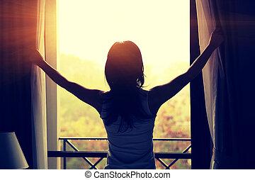jeune, femme, ouverture, rideaux, dans, a, chambre à...