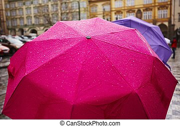 Rain in the city - People with umbrellas in heavy rain -...