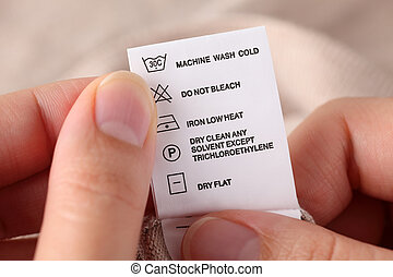 Clothes label with cleaning instructions - Womans hands...