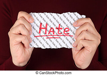 Hate - Piece of paper with red word Hate in the womans hands...