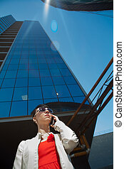 Beautiful young businesswoman is calling near skyscrapper. -...