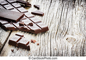 Dark chocolate tablets on old wood background