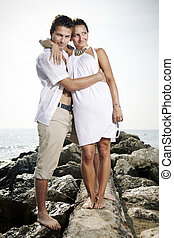 Summer couple by the sea - Couple on the baffle pier posing...