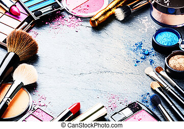 Colorful frame with various makeup products on dark...