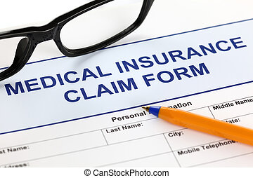 Medical insurance claim form with glasses and ballpoint pen....