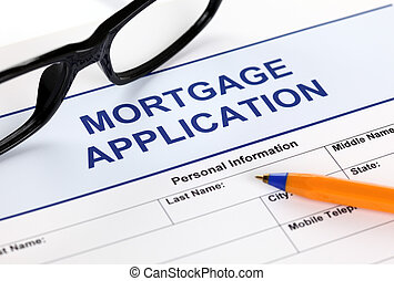 Mortgage application form with glasses and ballpoint pen.