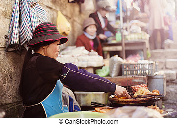 Asian market - Asian woman selling sausages on traditional...