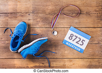 Running shoes on the floor - Pair of running shoes, medal...