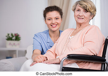 Woman sitting on a wheelchair - Smiling elder woman sitting...