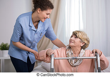 Senior woman using walking frame and supporting nurse