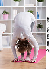 Stretched woman bending down - Vertical view of stretched...