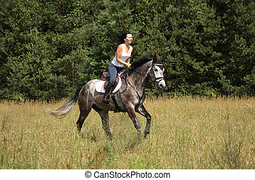 Beautiful woman riding gray horse in the forest - Beautiful...