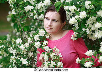 Woman surrounded by flowers - Portrait of a pretty young...