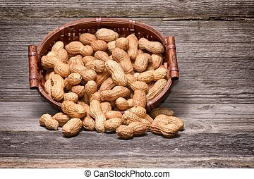 peanuts in basket on old wood background