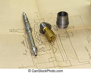 Machine parts and drawing - Machine parts of metal lying on...
