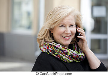 Mature beautiful blonde woman is calling on a cell phone,...