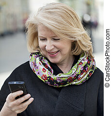 Mature blonde woman reads the message on the phone - Mature...