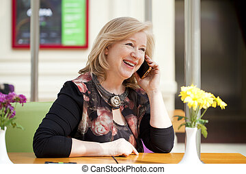 Mature beautiful woman is calling on a cell phone while...