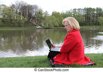 an elderly woman sitting with a laptop in a spring park