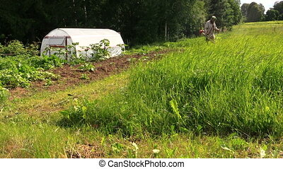 man cut grass trimmer - villager cut tall grass with...