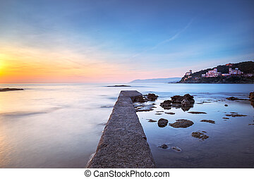 Castiglioncello bay concrete pier, rocks and sea on sunset...