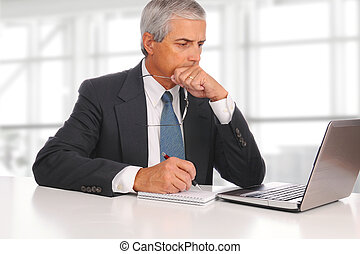 Mature Businessman Seated with Laptop - Mature businessman...
