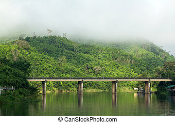 Bridge across river with mountain and fog