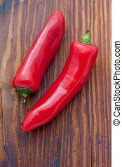 Two large red cayenne chili peppers on a wooden board