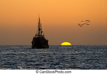 Pirate Ship Ocean Sunset - An old wooden pirate ship sits on...