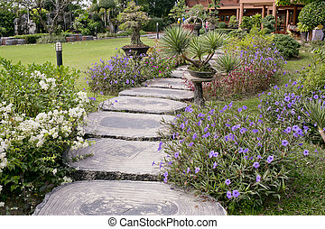Wooden stump path with beautiful flowers in park.