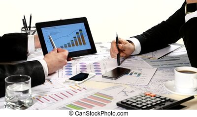 Financial charts on the table, developing a business project and analyzing market data information, tablet in business negotiations