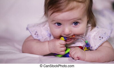 Baby eats rattle - Baby girl smiles and takes in her mouth...