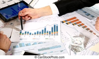 men discussing business charts sitting at the table, developing a business project and analyzing market data information