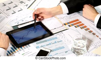 Business negotiations: a tablet with graphs on the table,...